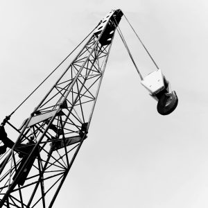 The boom and hook of a construction crane phorographed with sky background.